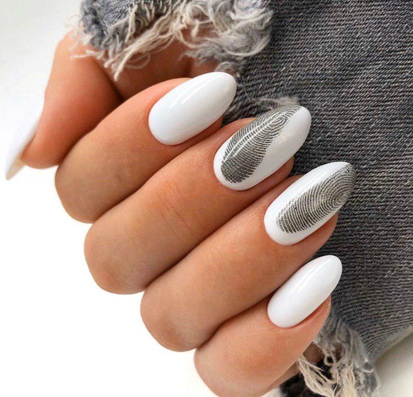 Белый маникюр с черными отпечатками пальцев на овальных ногтях