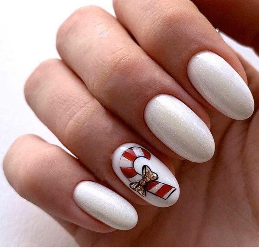 Маникюр на новый год в белом цвете с конфеткой на овальных ногтях