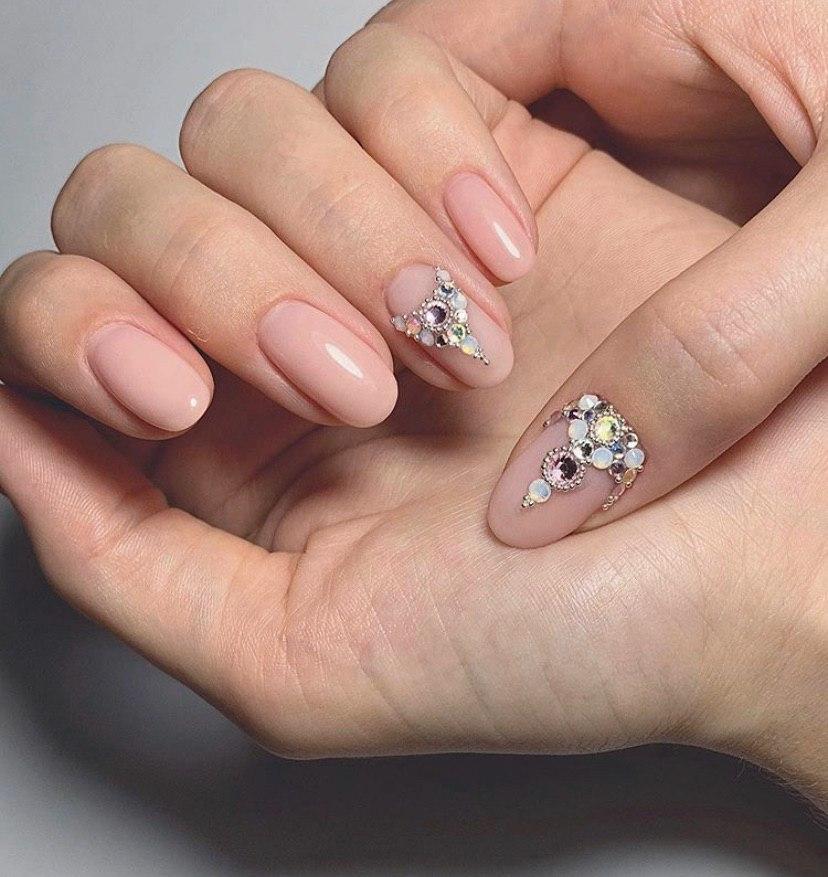 Маникюр нюдовый беж со стразами на овальных ногтях