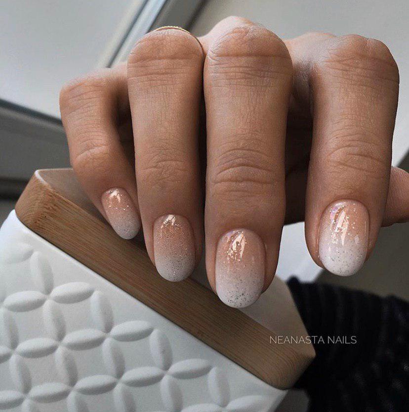 Маникюр омбре в бежево-белом цвете на коротких овальных ногтях с блестками