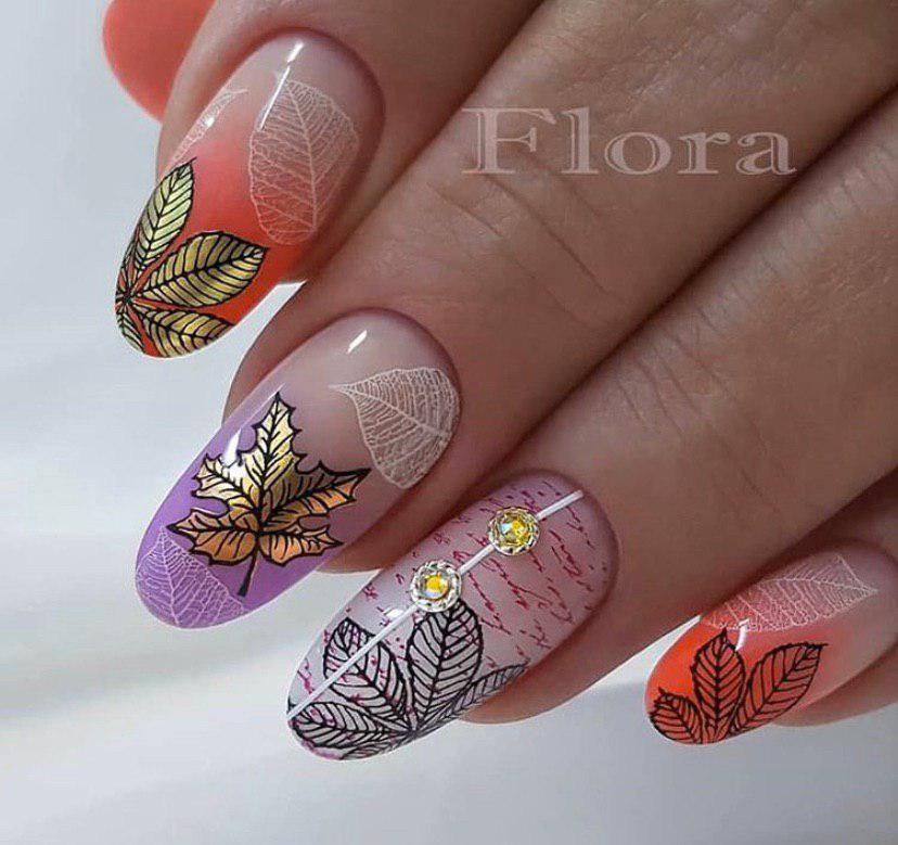 Маникюр с дизайном омбре с бежевой основой и листьями на осень на овальной форме ногтей