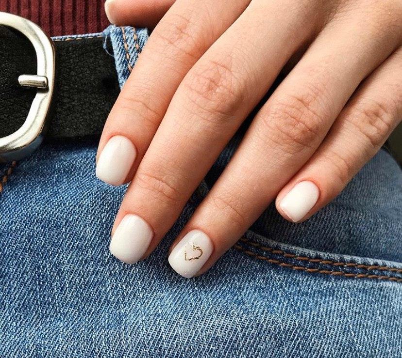 Молочный маникюр с нежным сердечком из золота на коротких ногтях