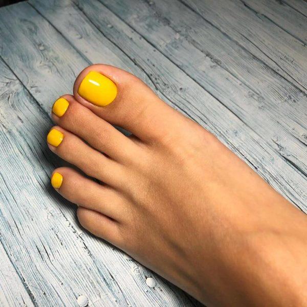 Однотонный желтый педикюр на море