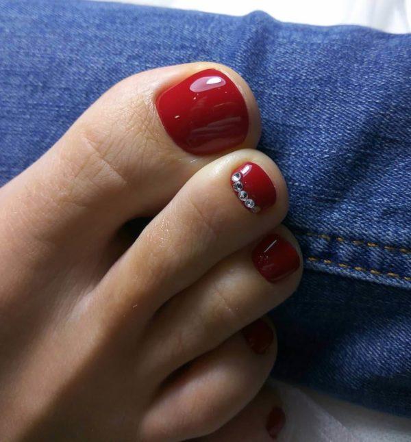 Красный педикюр со стразами на 1 пальце