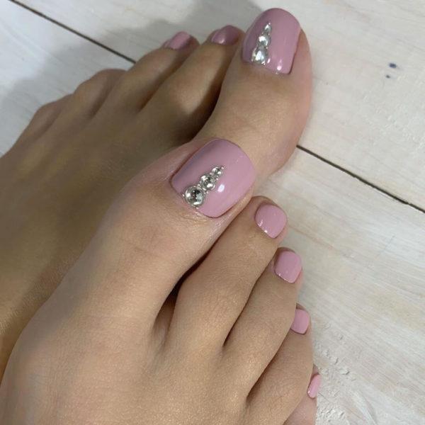 Розовый педикюр со стразами на большом пальце