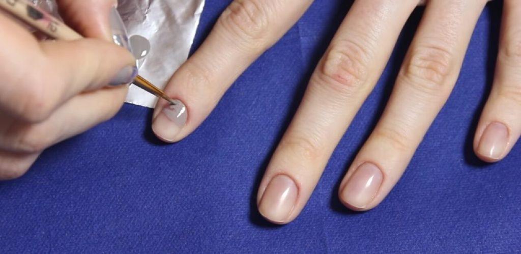 Нанести лак на половину ногтевой поверхности тонкой кистью